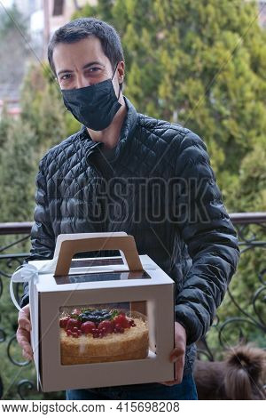 Young Smiling Man Stands In Front Of The Door Holding Cardboard Box With Holiday Cake Decorated With