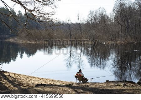 A Lone Fisherman Sits On The Shore In A Spring Reservoir And Catches Fish With A Fishing Rod