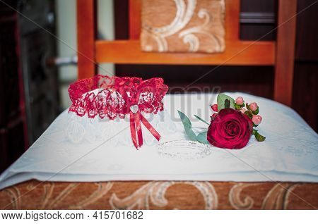 White With Red Garter And Red Rose Lying On The White Tissue
