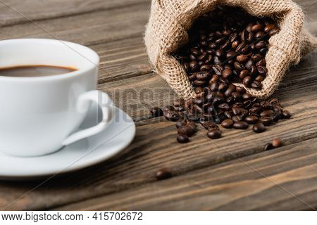 Hessian Sack Bag With Roasted Coffee Beans Near Cup On Blurred Foreground.