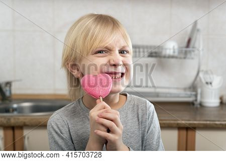 Fair-haired Boy Holds Heart-shaped Lollipop In His Hands