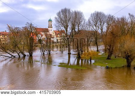 Germany, Regensburg On The Danube, Flood In Spring 2021,  Church With Clocks, Park In Foreground