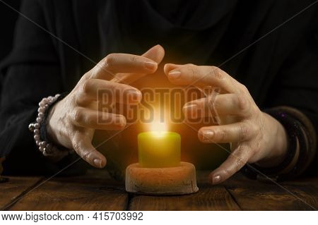 A Fortune-teller Or Oracle With Objects For Fortune-telling Holds A Burning Candle During The Sessio