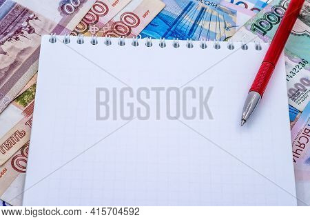 A Clean Slate Against The Backdrop Of Money. Rubles Notebook And Red Pen. Notepad On A Spring And A