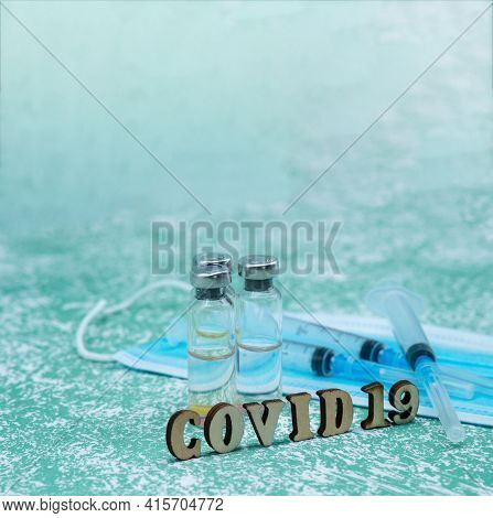 Prevention Of Seasonal Diseases. Medical Ampoules, Syringes, And A Mask On A Green Background. Vacci