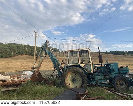 Rusty Excavator Working In Countryside. Weathered Excavator Digging Ground During Agricultural Works