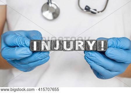 Injury - Word From Stone Blocks With Letters Holding By A Doctor's Hands In Medical Protective Glove