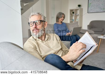 Happy Older Senior Man Husband Wearing Glasses Reading Book Relaxing Sitting On Couch At Home With M