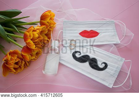 Two Disposable Protective Masks With Painted Mustache And Lips, Two Wedding Rings And Sanitizer Next