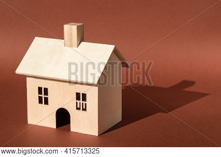 Home, Sweet Home. Wooden House Building Miniature Model With Shadow On Brown Background. Buying New