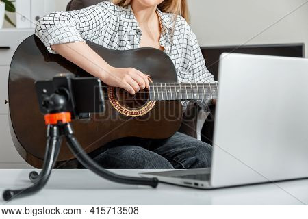 Young Woman Plays Acoustic Guitar At Home For Online Audience On Laptop And Smartphone. Online Class