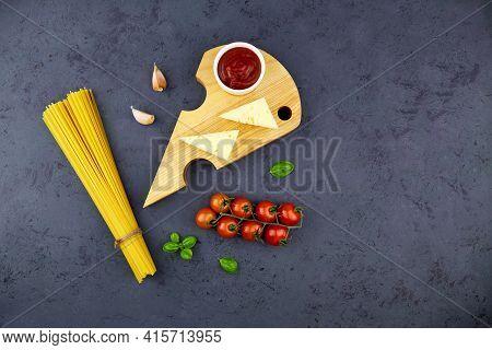 Ingredients For Homemade Pasta: Linguini, Tomato, Sauce, Parmesan, Basil On Dark Grey Background. To