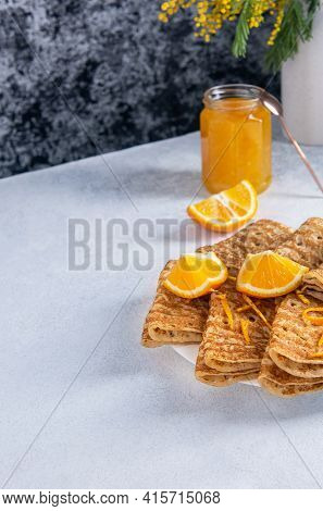 Folded Baked Crepes Or Blinis In A Plate With Orange Slices And Jam On A Light Background With Copy