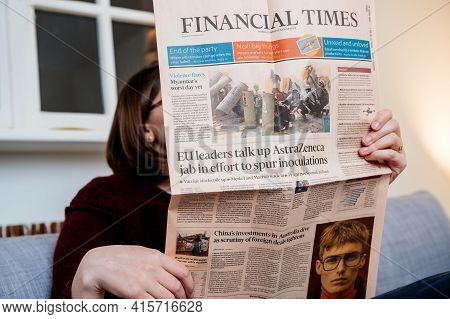 Paris, France - Mar 3, 2021: Woman Reading In Living Room Next To Her Cat The Latest Financial Times