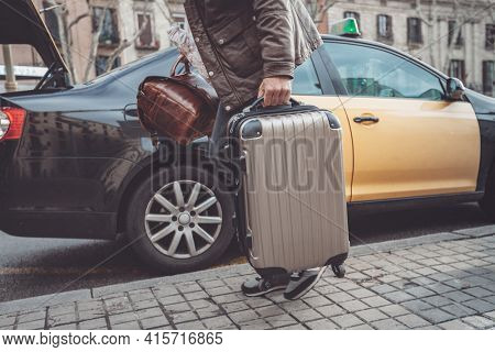 Business man leaving for airplane departure boarding taxi with carry-on luggages packing truck of car for travel holiday vacation.