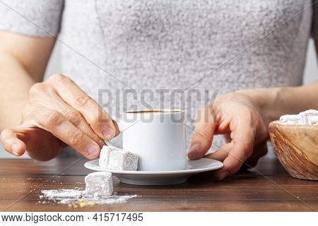 A Caucasian Turkish Woman Is Drinking Traditional Turkish Coffee From Special Cup. The Coffee Is Ser