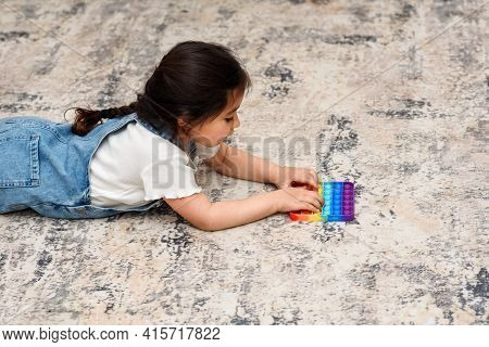 Young Little Girl Lies On The Floor At Home Playing Poppit-new Fidget Toy, Popular With Kids, Helps