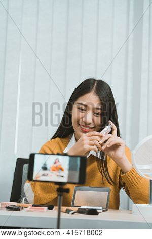 Young Asian Woman Vlogging About Cosmetics Skin Care Items Products On Table With Her Video Camera A