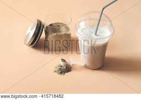 Whey Drink In Plastic Cup And A Jar With Chocolate Protein Powder And A Scoop On A Table. Protein Su
