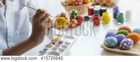 Happy Asian Woman Painting Eggs For Eastertime At Home. Family Preparing For Easter.