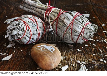 A Close Up Image Of Two White Sage Smudge Bundles And Reiki Healing Symbol On A Dark Wooden Table To