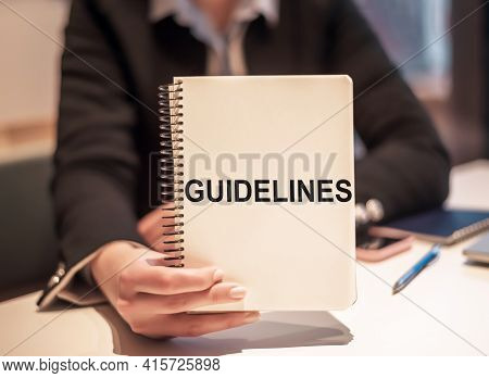 Business Woman Holds A Notebook With The Text Guidelines.