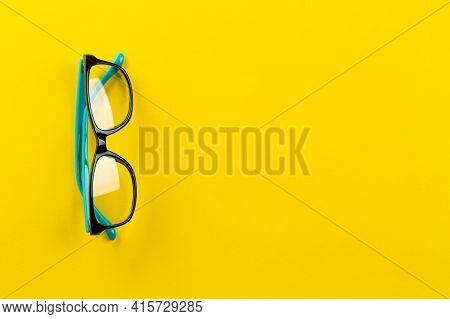 Eyeglasses On Yellow Background, Myopia Or Presbyopia. Eyesight Correction. Fashion Accessories. Spa