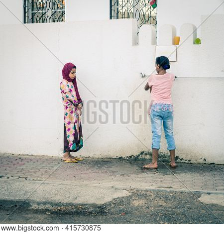 Muscat, Oman, December 3, 2016: Two girls by a water spigot outside of a mosque in the old town in Muscat, Oman