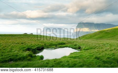 Lonely tourist near small lake looks at foggy islands in Atlantic ocean
