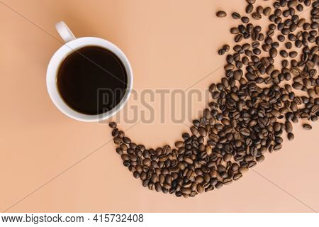 Beige Flat Lay Background With White Ceramic Cup Of Coffee, Roasted Coffee Beans Steam Shape From Ho