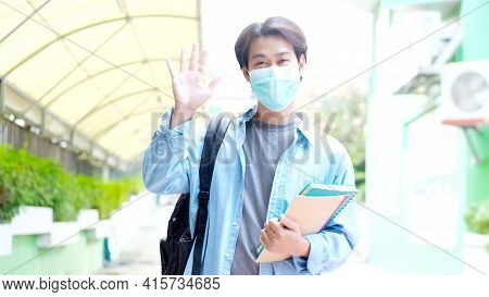 Young Asian Campus Student Man Wearing Protection Mask Looking At Camera While Walking In Campus, Co