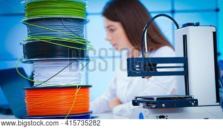 Young woman in design office with 3d printer and plastic filament printing concept model