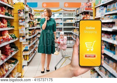 Shopping. A Young Woman Chooses Products, Holding A Grocery Cart With A Baby Sitting In It. View Amo