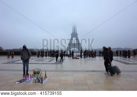 Paris, France - November 22, 2018: Eiffel Tower hidden in low clouds, Many people on Eiffel Tower viewing platform at Palais de Chaillot, Tourist with suitcase on wheels, Street souvenir vendor