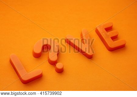 L...ve Word Is Laid Out In Orange Letters On An Orange Background. Question Love Or Livev. The Conce