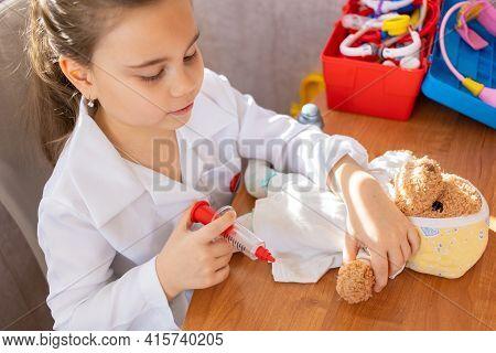 Pretty Cute Preschool Child Girl Wearing In White Medical Uniform Playing With Sick Teddy Bear Toy A