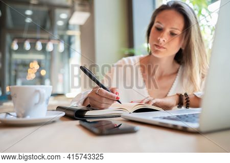 Young Businesswoman Writing In Her Notebook In A Coffee Shop.focus On The Hand And Notebook