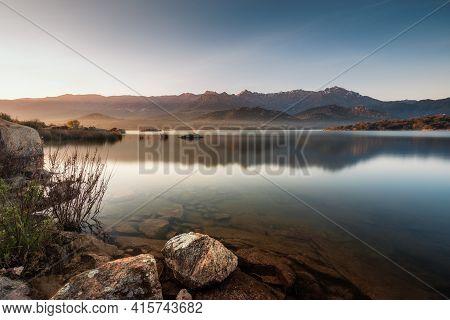 Dawn Breaking Over The Lac De Codole At Regino In The Balagne Region Of Corsica With The Snow Capped