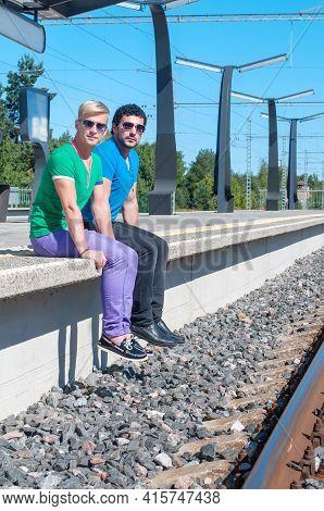 Shot Of Two Young Men Sitting On Platform