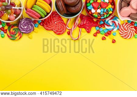 Various sweets assortment. Candy, bonbon and lollipop on yellow background. Top view flat lay with copy space