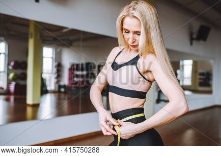 Beautiful Blonde Woman Measuring Her Athletic Fit Abdomenbelly With Yellow Tape. Successful Weight L