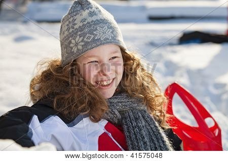 Relaxed Girl In Winter Cloths With Red Sledge
