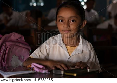 Bluff, Nicaragua. 03-17-2019. Portrait Girl Looking At The Camera Studying At School In The Town Of