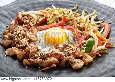 Teppan japanese cuisine - Teppanyaki Chicken with Egg and Vegetables. Sliced chicken breast on heat teppanyaki hot plate grill with sesame seed