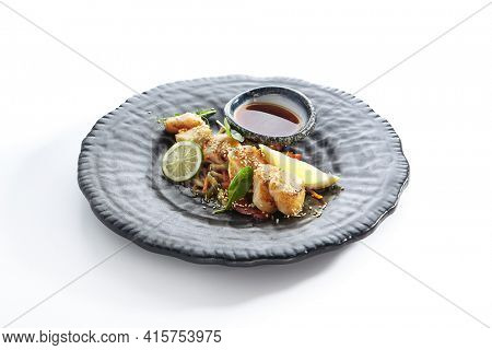 Teppanyaki Style Scallop - Grilled Sea Scallop with Soy Sauce and Vegetables. Japanese Teppanyaki Scallop garnished with lemon and fresh basil leaf. Black asian plate isolated on white background