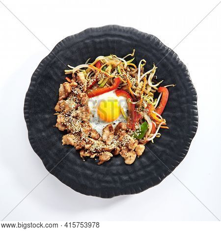 Teppan japanese cuisine - Teppanyaki Chicken with Egg and Vegetables. Sliced chicken breast on heat teppanyaki hot plate grill with sesame seed. Top view