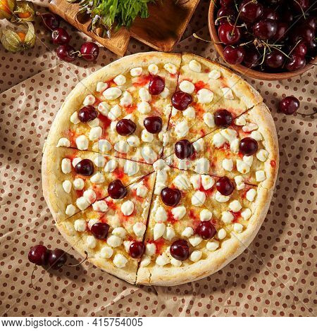 Cherry Cheese Pizza - homemade dessert pizza is made with a buttery dough, cherry and cream cheese. Sweet pizza on paper with ripe sweet cherry and wooden plate. Dessert lunch in rustic style