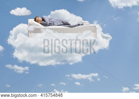 Man sleeping peacefully up in the clouds floating on his bed