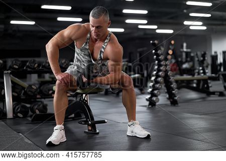 Muscular Athletic Bodybuilder Fitness Model Sitting Bench Training Biceps Lift Dumbbells Through Pai