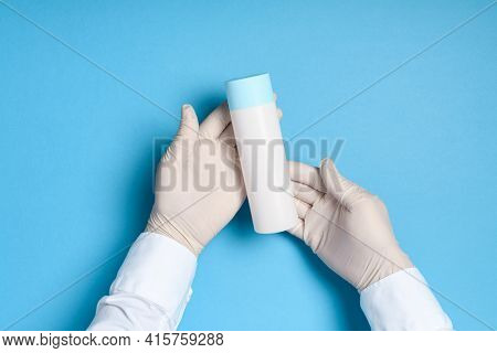 hands in medical gloves on a blue background, abstract white bottle with sanitizer or disinfector, health care prevention of coronavirus infection or other viruses